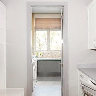 Klassisk inredning av en mellanstor grå l-formad grått tvättstuga enbart för tvätt, med en undermonterad diskho, släta luckor, turkosa skåp, bänkskiva i koppar, beige väggar, klinkergolv i porslin och brunt golv