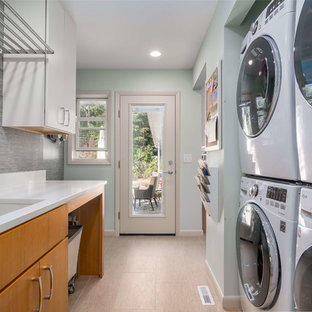 Inspiration for a mid-sized transitional galley ceramic floor and beige floor dedicated laundry room remodel in Other with a single-bowl sink, flat-panel cabinets, light wood cabinets, granite countertops, blue walls and a stacked washer/dryer