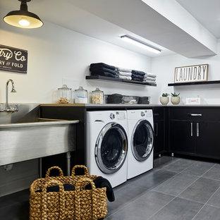 Foto på en stor funkis l-formad tvättstuga enbart för tvätt, med en allbänk, släta luckor, svarta skåp, vita väggar, klinkergolv i porslin, en tvättmaskin och torktumlare bredvid varandra och grått golv