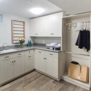 Immagine di una sala lavanderia di medie dimensioni con lavello sottopiano, ante lisce, ante in legno chiaro, top in cemento, pareti grigie, pavimento in gres porcellanato, lavatrice e asciugatrice affiancate, pavimento beige e top grigio