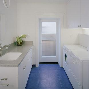 Inspiration för stora moderna parallella grovkök, med en undermonterad diskho, släta luckor, vita skåp, bänkskiva i koppar, vita väggar, klinkergolv i keramik, en tvättmaskin och torktumlare bredvid varandra och blått golv
