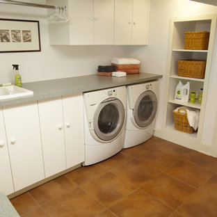 Example of a small arts and crafts l-shaped ceramic floor dedicated laundry room design in Minneapolis with a drop-in sink, flat-panel cabinets, laminate countertops and white walls