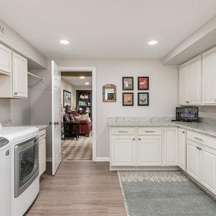 Idee per una grande sala lavanderia chic con ante con bugna sagomata, ante bianche, top in granito, pareti grigie, pavimento in vinile, lavatrice e asciugatrice affiancate, pavimento beige e top multicolore