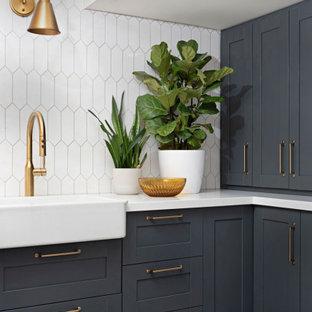 Inredning av en lantlig vita vitt tvättstuga, med en rustik diskho, skåp i shakerstil, blå skåp, bänkskiva i kvarts, linoleumgolv, en tvättmaskin och torktumlare bredvid varandra och grått golv