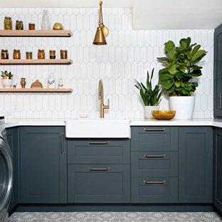 Inspiration för lantliga vitt tvättstugor, med en rustik diskho, skåp i shakerstil, blå skåp, bänkskiva i kvarts, linoleumgolv, en tvättmaskin och torktumlare bredvid varandra och grått golv