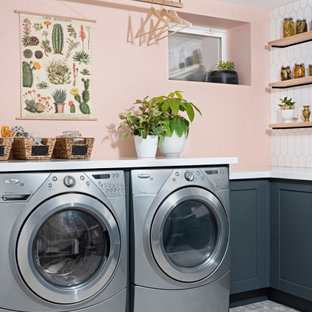 Photo of a country l-shaped laundry room in Toronto with shaker cabinets, blue cabinets, quartz benchtops, linoleum floors, a side-by-side washer and dryer, grey floor, white benchtop and pink walls.