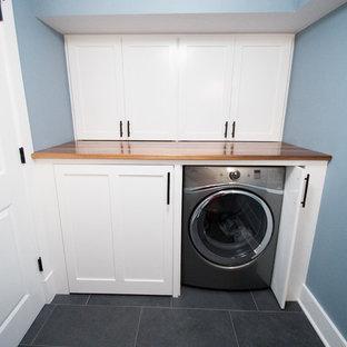 Foto på en mellanstor vintage linjär tvättstuga enbart för tvätt, med blå väggar, skåp i shakerstil, vita skåp, träbänkskiva, skiffergolv och en tvättmaskin och torktumlare bredvid varandra