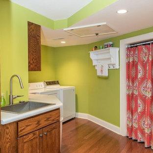 Imagen de cuarto de lavado lineal, ecléctico, de tamaño medio, con fregadero encastrado, armarios estilo shaker, puertas de armario de madera en tonos medios, encimera de laminado, paredes verdes, suelo de madera oscura y suelo marrón