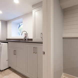Example of a mid-sized transitional single-wall ceramic tile and beige floor utility room design in Chicago with an undermount sink, flat-panel cabinets, gray cabinets, granite countertops, gray walls, a side-by-side washer/dryer and black countertops