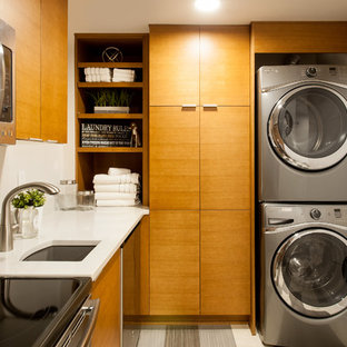 This is an example of a large modern utility room in Seattle with a submerged sink, flat-panel cabinets, light wood cabinets, quartz worktops, white walls, ceramic flooring and a stacked washer and dryer.