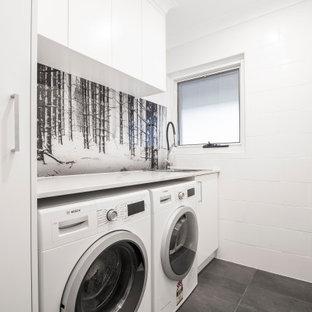 Exempel på ett stort modernt vit linjärt vitt grovkök med garderob, med luckor med infälld panel, vita skåp, vita väggar, svart golv, en nedsänkt diskho, bänkskiva i kvarts, rött stänkskydd, glaspanel som stänkskydd och klinkergolv i keramik