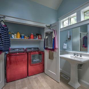 Foto på ett mellanstort vintage linjärt grovkök, med blå väggar, ljust trägolv och tvättmaskin och torktumlare byggt in i ett skåp