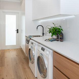 Ispirazione per una grande sala lavanderia design con lavello sottopiano, ante in legno chiaro, top in quarzo composito, pareti bianche, parquet chiaro, lavatrice e asciugatrice affiancate e top bianco