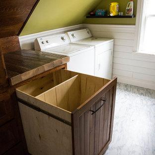 Immagine di una lavanderia multiuso stile rurale di medie dimensioni con ante a filo, ante in legno bruno, top in legno, pareti verdi, pavimento in vinile, lavatrice e asciugatrice affiancate, pavimento bianco e top marrone