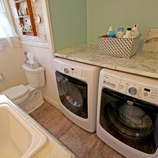 Foto di una piccola lavanderia multiuso country con lavello da incasso, ante con riquadro incassato, ante bianche, top in laminato, pareti verdi e lavatrice e asciugatrice affiancate