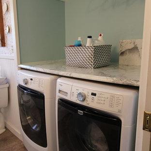 Foto på en liten lantlig u-formad tvättstuga, med en nedsänkt diskho, vita skåp, laminatbänkskiva, gröna väggar och en tvättmaskin och torktumlare bredvid varandra