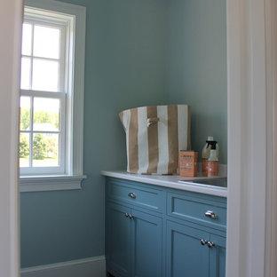 Immagine di una grande sala lavanderia chic con ante blu, pareti blu, pavimento grigio e top bianco