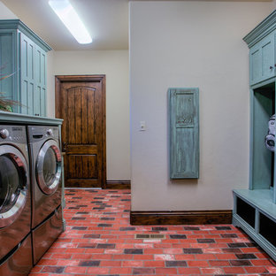 This is an example of a large country galley utility room in Oklahoma City with brick floors, blue cabinets, shaker cabinets, wood benchtops, beige walls, a side-by-side washer and dryer, red floor and blue benchtop.