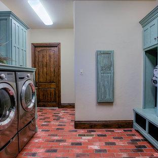 На фото: большая параллельная универсальная комната в стиле рустика с кирпичным полом, синими фасадами, фасадами в стиле шейкер, деревянной столешницей, бежевыми стенами, со стиральной и сушильной машиной рядом, красным полом и синей столешницей с