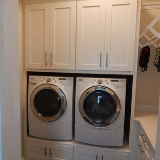 Example of a large classic l-shaped dark wood floor laundry room design in Charlotte with a farmhouse sink, shaker cabinets, white cabinets, granite countertops, gray backsplash and glass tile backsplash