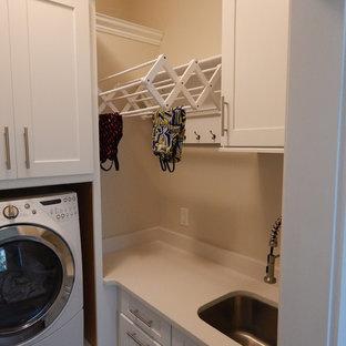 Klassisk inredning av en stor l-formad tvättstuga, med en rustik diskho, skåp i shakerstil, vita skåp, granitbänkskiva, grått stänkskydd, stänkskydd i glaskakel och mörkt trägolv