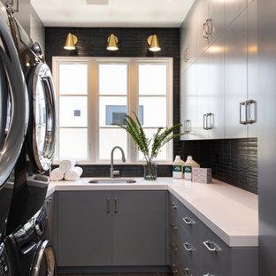 Foto di una sala lavanderia classica di medie dimensioni con lavello sottopiano, ante lisce, ante grigie, top in quarzo composito, paraspruzzi nero, paraspruzzi con piastrelle in ceramica, pareti nere, pavimento in vinile, lavatrice e asciugatrice a colonna, pavimento grigio e top bianco