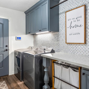 Large transitional single-wall laundry cupboard in Houston with raised-panel cabinets, blue cabinets, grey walls, a side-by-side washer and dryer, brown floor and grey benchtop.