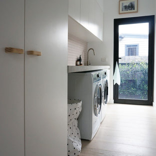 Design ideas for a small contemporary single-wall dedicated laundry room in Melbourne with an undermount sink, concrete benchtops, a side-by-side washer and dryer, flat-panel cabinets, white cabinets, light hardwood floors and white walls.