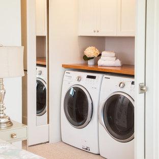 Bild på en liten vintage liten tvättstuga, med skåp i shakerstil, vita skåp, träbänkskiva, vita väggar, heltäckningsmatta och en tvättmaskin och torktumlare bredvid varandra