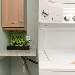 Cette image montre une buanderie linéaire marine de taille moyenne avec un placard, un placard à porte shaker, des portes de placard en bois clair, un plan de travail en quartz, un mur vert, un sol en vinyl, des machines superposées, un sol gris et un plan de travail vert.