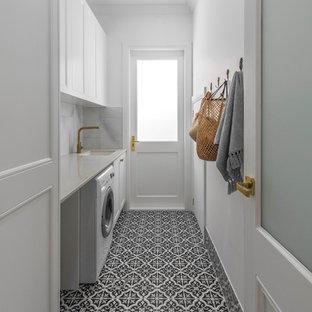 Idéer för en stor maritim vita linjär tvättstuga enbart för tvätt, med en undermonterad diskho, vita skåp, vita väggar, klinkergolv i keramik, en tvättmaskin och torktumlare bredvid varandra och svart golv