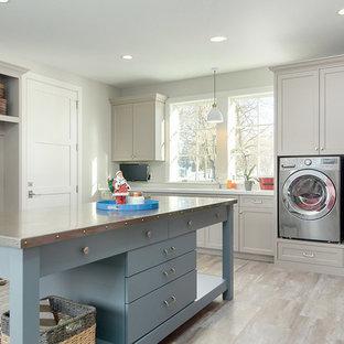 Ispirazione per una grande lavanderia multiuso costiera con top in quarzo composito, pareti grigie, pavimento in laminato, lavatrice e asciugatrice affiancate, ante in stile shaker, ante grigie, pavimento grigio e top bianco