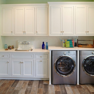 Inspiration for a beach style single-wall brown floor laundry room remodel in Minneapolis with green walls, a drop-in sink, recessed-panel cabinets, white cabinets and white countertops