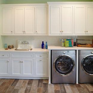 Ispirazione per una lavanderia stile marino con pareti verdi, lavello da incasso, ante con riquadro incassato, ante bianche, lavatrice e asciugatrice affiancate, pavimento marrone e top bianco