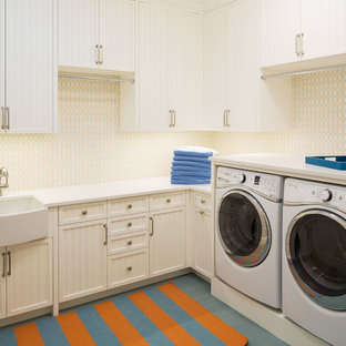 Dedicated laundry room - beach style l-shaped dedicated laundry room idea in Minneapolis with a farmhouse sink, recessed-panel cabinets, white cabinets, multicolored walls and a side-by-side washer/dryer
