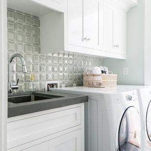 Ispirazione per una sala lavanderia tradizionale di medie dimensioni con lavello sottopiano, ante in stile shaker, ante bianche, top in superficie solida, pavimento in gres porcellanato, lavatrice e asciugatrice affiancate, pavimento grigio e pareti grigie