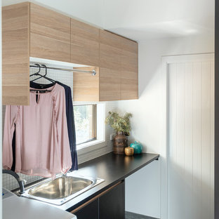 This is an example of a small beach style galley separated utility room in Other with a built-in sink, black cabinets, laminate countertops, white walls, porcelain flooring, grey floors and black worktops.