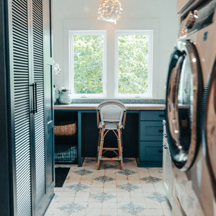 Huge beach style ceramic tile and multicolored floor utility room photo in Other with blue cabinets, wood countertops, blue backsplash, glass tile backsplash, white walls, a stacked washer/dryer and brown countertops