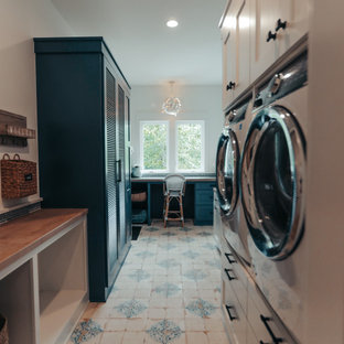 Utility room - huge coastal ceramic tile and multicolored floor utility room idea in Other with blue cabinets, wood countertops, blue backsplash, glass tile backsplash, white walls, a stacked washer/dryer and brown countertops
