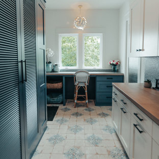 Expansive beach style utility room in Other with blue cabinets, wood benchtops, blue splashback, glass tile splashback, white walls, ceramic floors, a stacked washer and dryer, multi-coloured floor and brown benchtop.