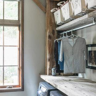 Cette image montre une buanderie chalet dédiée et de taille moyenne avec un placard sans porte, des portes de placard en bois brun, un plan de travail en bois, un mur blanc, un sol en bois foncé, des machines côte à côte et un sol gris.