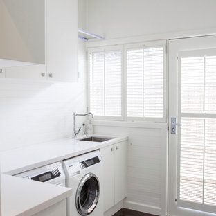 Laundry room - contemporary dark wood floor laundry room idea in Melbourne with white cabinets, a side-by-side washer/dryer and white countertops