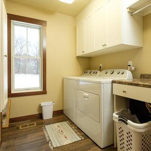 Esempio di una sala lavanderia tradizionale di medie dimensioni con ante in stile shaker, ante bianche, top in laminato, pareti beige, pavimento in legno massello medio, lavatrice e asciugatrice affiancate e pavimento marrone