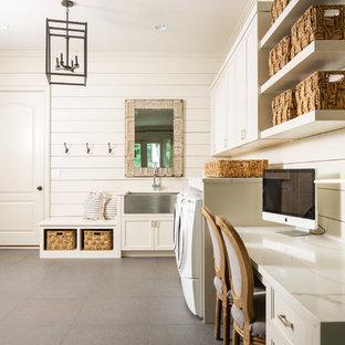 Foto på ett mycket stort lantligt vit l-format grovkök, med en rustik diskho, luckor med infälld panel, vita skåp, bänkskiva i kvartsit, vita väggar, en tvättmaskin och torktumlare bredvid varandra och grått golv