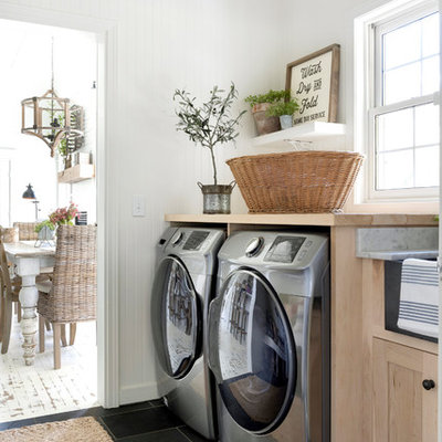 Inspiration for a farmhouse black floor laundry room remodel in Minneapolis with shaker cabinets, light wood cabinets, wood countertops, white walls, a side-by-side washer/dryer and beige countertops