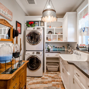 Inspiration for a cottage l-shaped red floor dedicated laundry room remodel in Other with a farmhouse sink, raised-panel cabinets, white cabinets, gray walls, a stacked washer/dryer and gray countertops