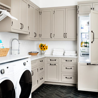 This is an example of a traditional l-shaped utility room in New York with white walls, slate flooring, a side by side washer and dryer, white worktops, shaker cabinets, beige cabinets and black floors.