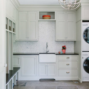 Design ideas for a large traditional l-shaped separated utility room in Chicago with a belfast sink, recessed-panel cabinets, white cabinets, composite countertops, white walls, marble flooring, a concealed washer and dryer and grey floors.