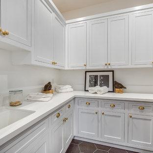 Idee per una piccola lavanderia multiuso classica con lavello da incasso, ante in stile shaker, ante bianche, pareti bianche, pavimento in terracotta, pavimento rosso, top bianco e top in marmo