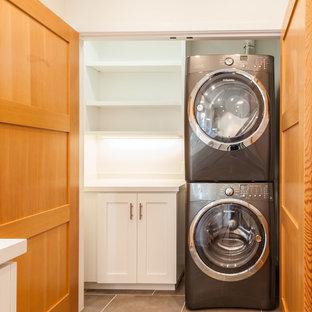 Immagine di una piccola sala lavanderia chic con ante in stile shaker, pareti bianche, pavimento in travertino, lavatrice e asciugatrice a colonna e ante bianche